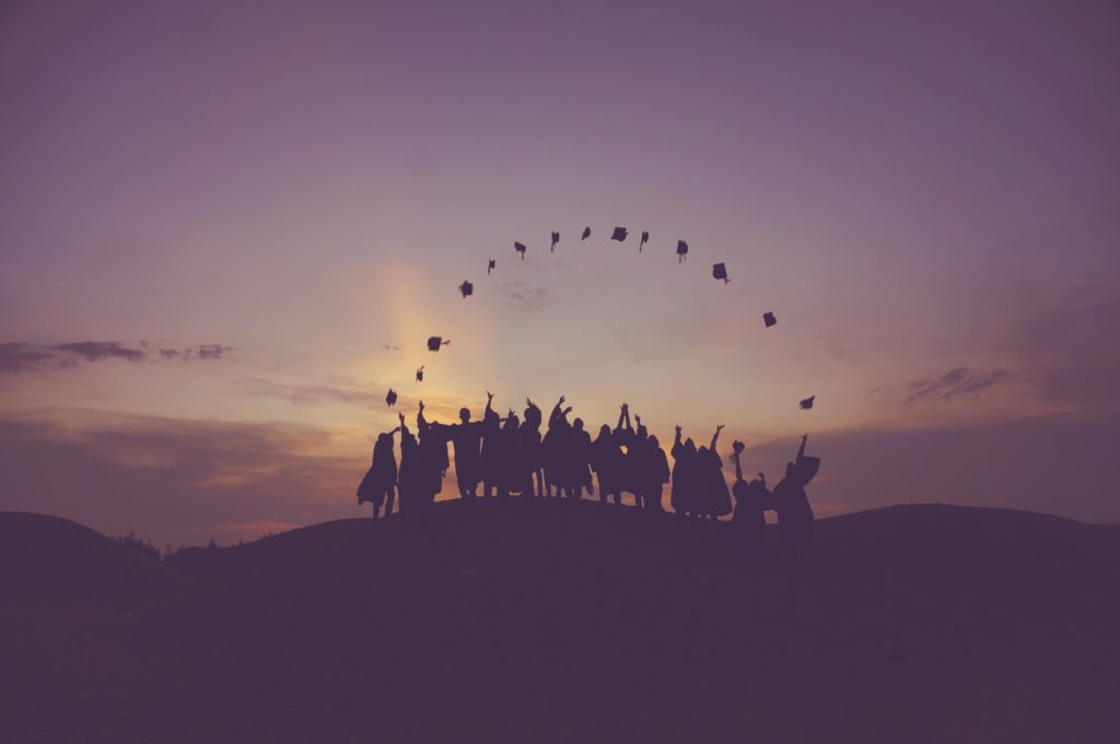 Graduates throwing their caps in the air during a sunset.