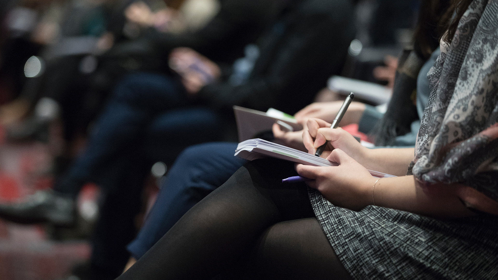 A group of people taking notes during a talk.